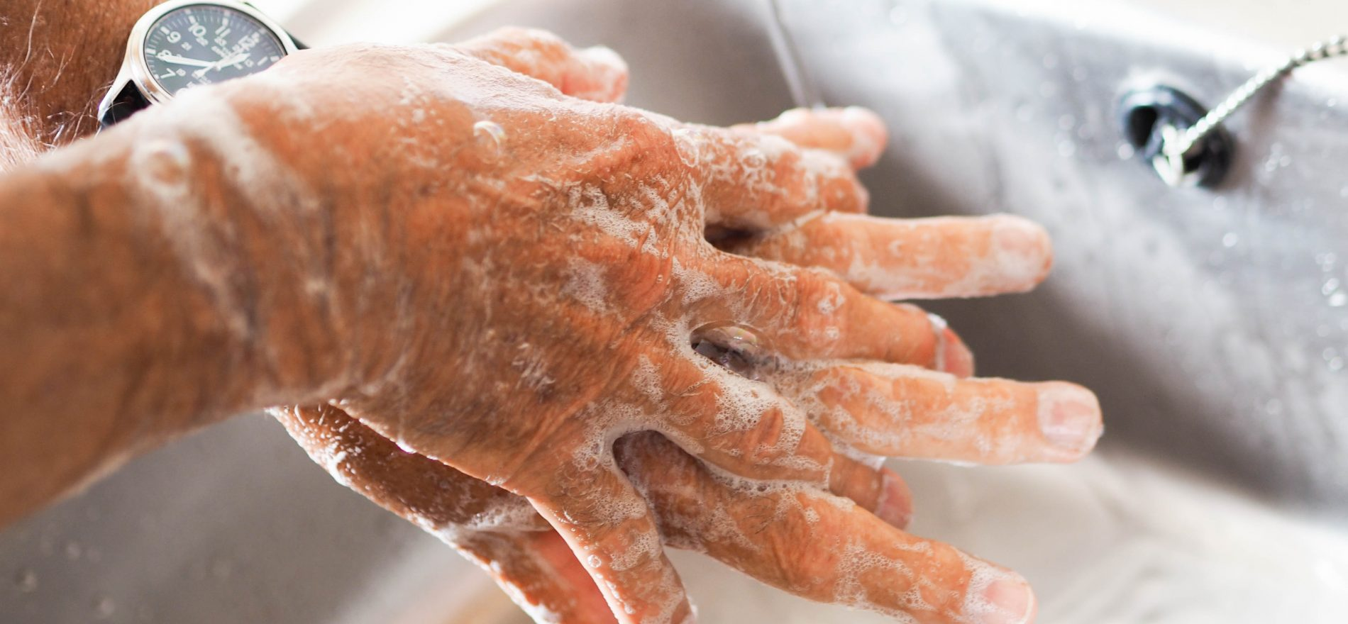person washing hands with liquid soap